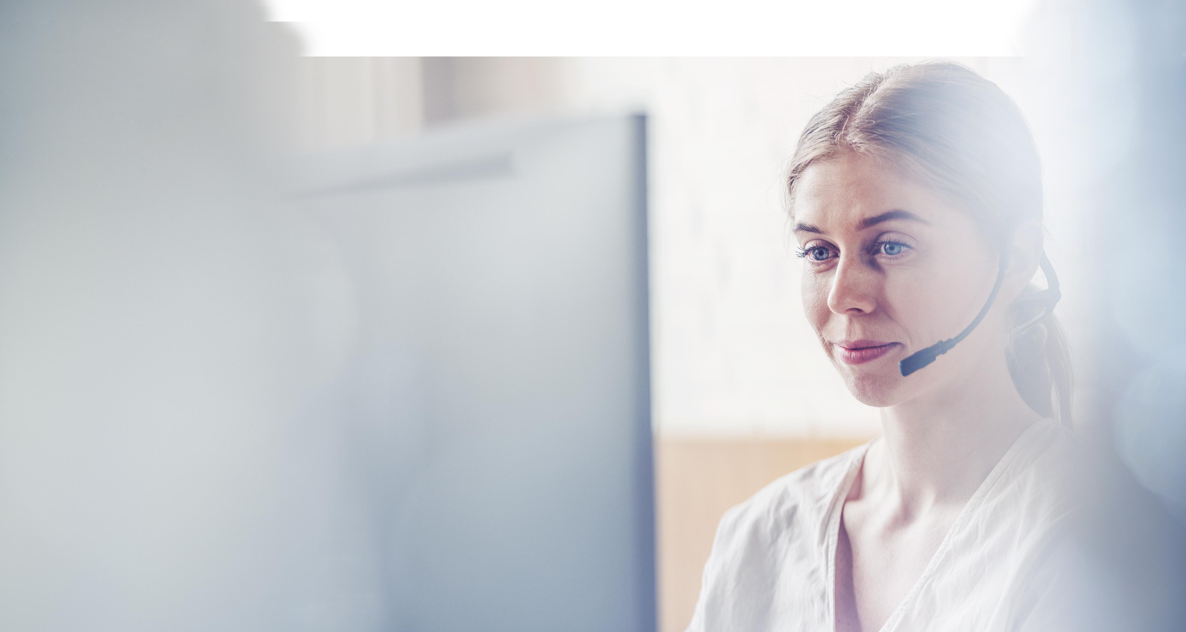 Kvinna med headset framför dator
